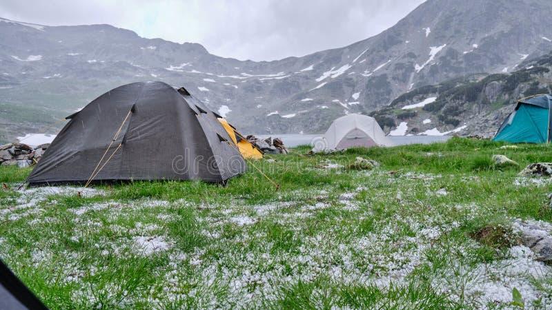 Barracas durante a saraiva e a chuva fria no verão, meio-dia no lago Bucura, montanhas de Retezat Vista do interior de uma barrac fotografia de stock