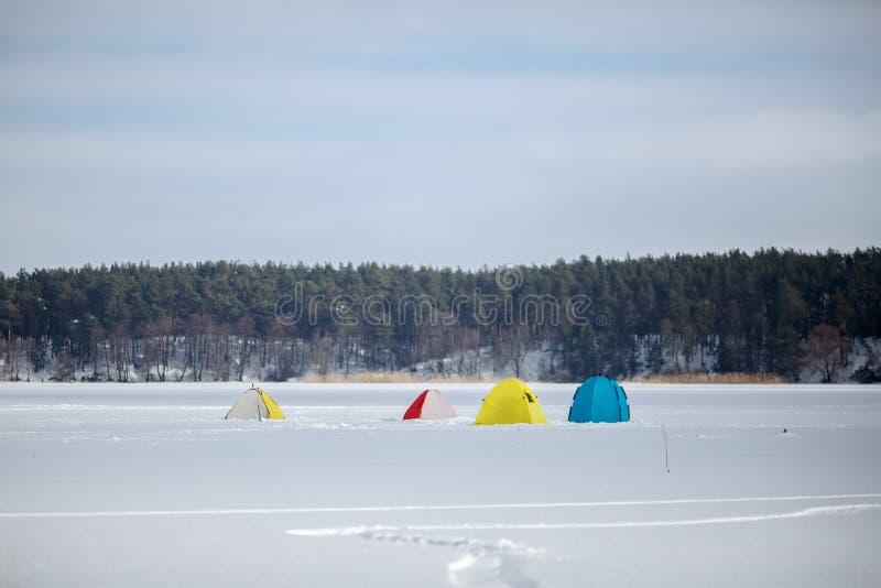 Barracas na pesca do inverno em um lago congelado foto de stock
