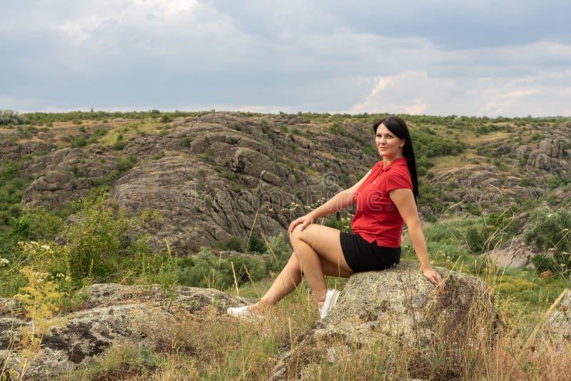 Barranco grande del granito Pueblo Aktove ucrania Paisaje de piedra hermoso Mujer 35 años del turista moreno en el barranco imagenes de archivo