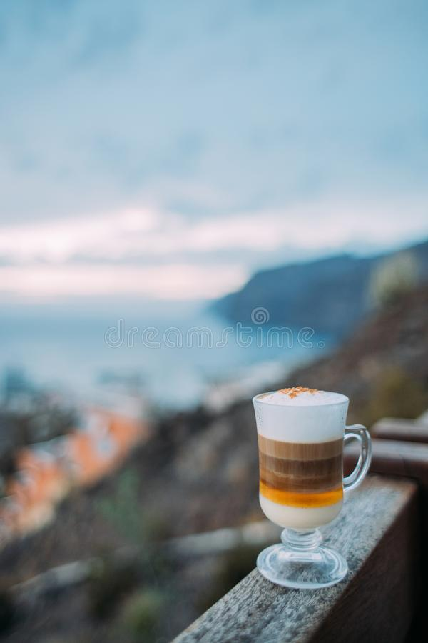 Barraquito, traditional coffee variety of Tenerife on background of ocean and harbor Los Gigantes, Canary Islands, Spain stock photos
