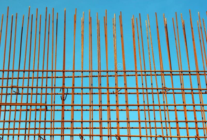 Barras de aço do reforço contra o fundo do céu azul no construc fotos de stock royalty free