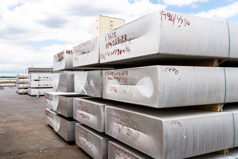Barras de alumínio pesadas que encontram-se em se na pilha no quadrado de uma fundição de alumínio imagens de stock royalty free