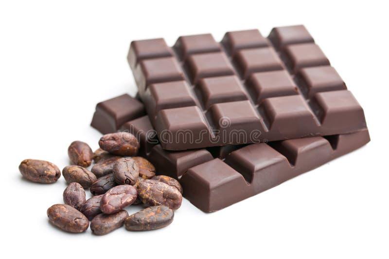 Barras de chocolate e feijões de cacau escuros imagens de stock royalty free