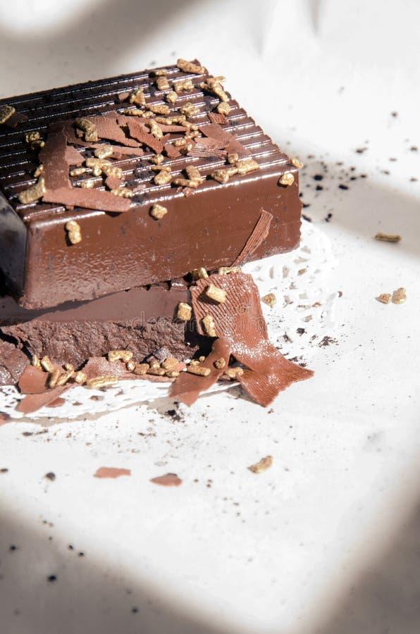 Barras de chocolate escuras empilhadas com pepitas de ouro imagens de stock royalty free