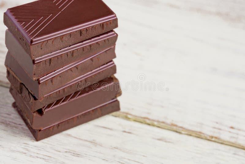 Barras de chocolate na tabela de madeira Partes quebradas de chocolate escuro Fundo do alimento fotos de stock royalty free