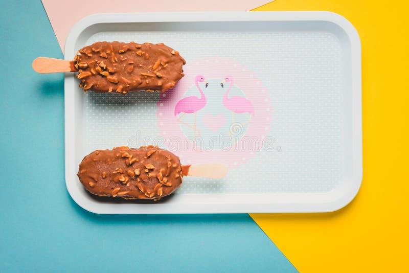 Barras de gelado de chocolate da sobremesa com porcas, vara de madeira no fundo pastel azul e amarelo Esquimó no vintage azul fotos de stock