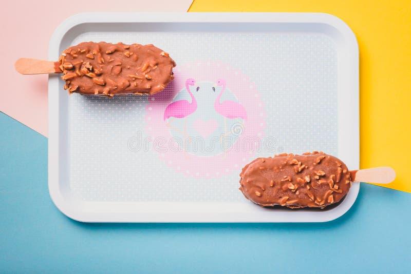Barras de gelado de chocolate da sobremesa com porcas, vara de madeira no fundo pastel azul e amarelo Esquimó no vintage azul foto de stock