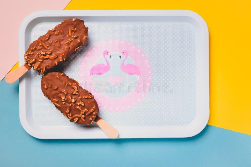 Barras de gelado de chocolate da sobremesa com porcas, vara de madeira no fundo pastel azul e amarelo Esquimó no vintage azul foto de stock royalty free