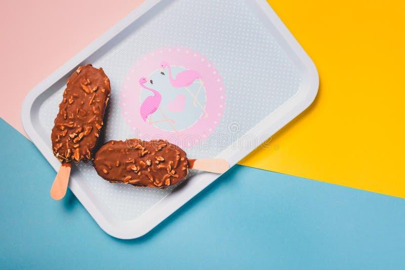 Barras de gelado de chocolate da sobremesa com porcas, vara de madeira no fundo pastel azul e amarelo Esquimó no vintage azul imagens de stock royalty free