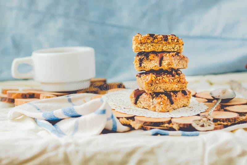Barras de granola hechas en casa orgánicas con caramelo y chocolate de la fecha de la sal en fondo azul Foco selectivo Una taza d imágenes de archivo libres de regalías