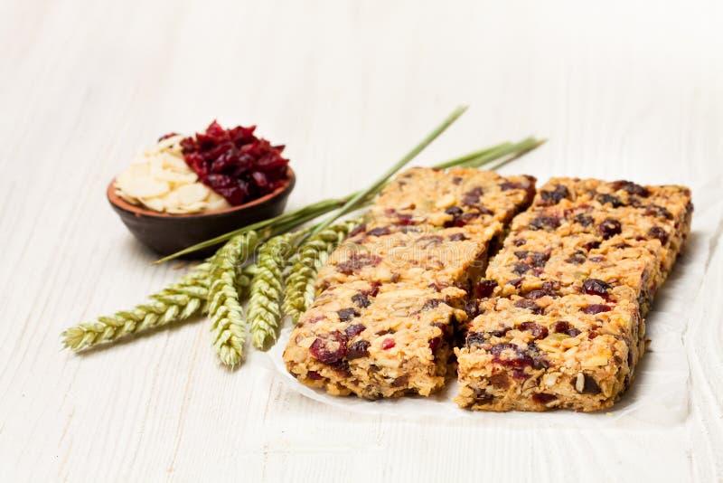 Barras de granola saudáveis da proteína com bagas e as porcas secadas no whi fotos de stock