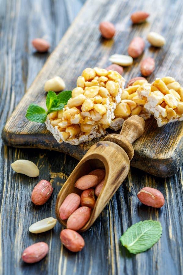 Barras de la miel con cacahuetes y una cucharada de madera foto de archivo libre de regalías