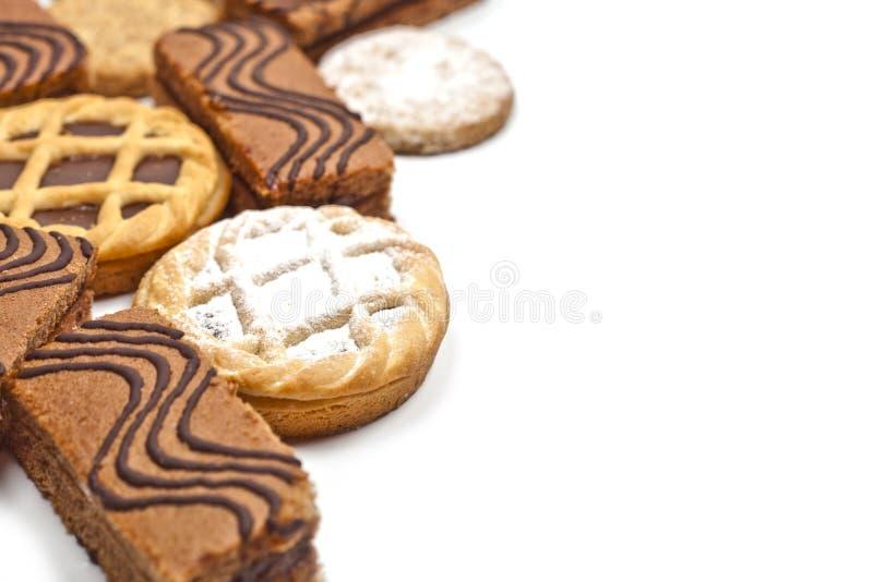 Barras de la torta llenadas de crema, de galletas de la avena y de tartas con el chocolate oscuro en el fondo blanco imagen de archivo