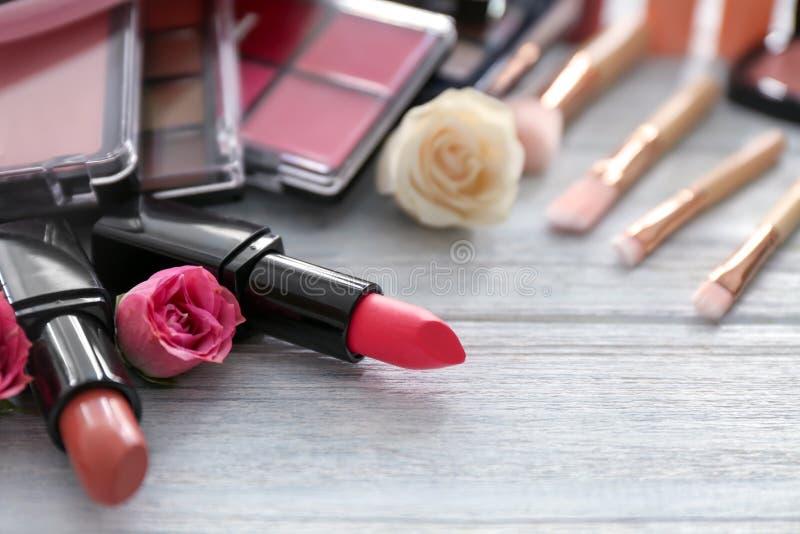 Barras de labios con los cosméticos decorativos en la tabla de madera imagen de archivo libre de regalías