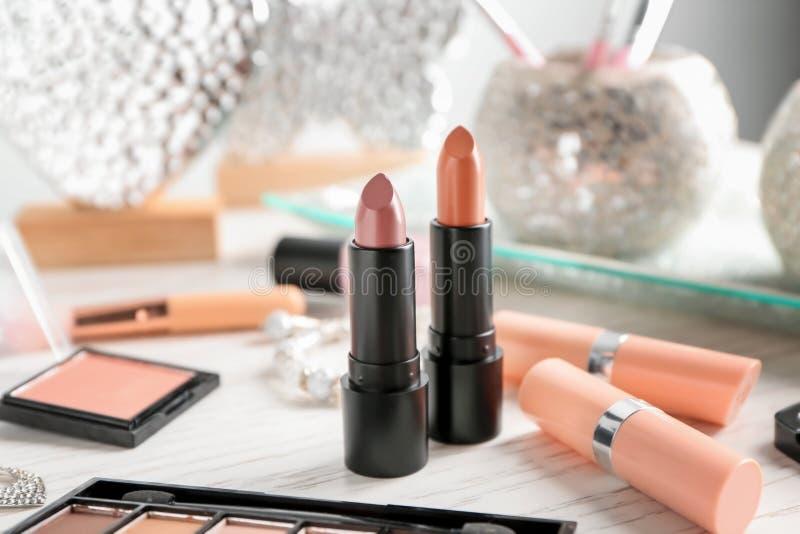 Barras de labios y otros cosméticos en la tabla fotos de archivo