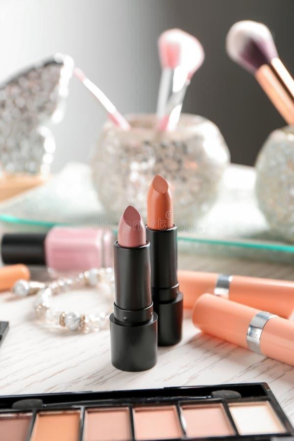 Barras de labios y otros cosméticos en la tabla imágenes de archivo libres de regalías