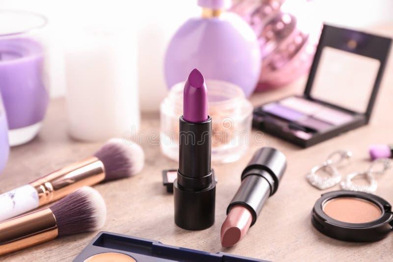 Barras de labios y otros cosméticos en la tabla imagen de archivo libre de regalías