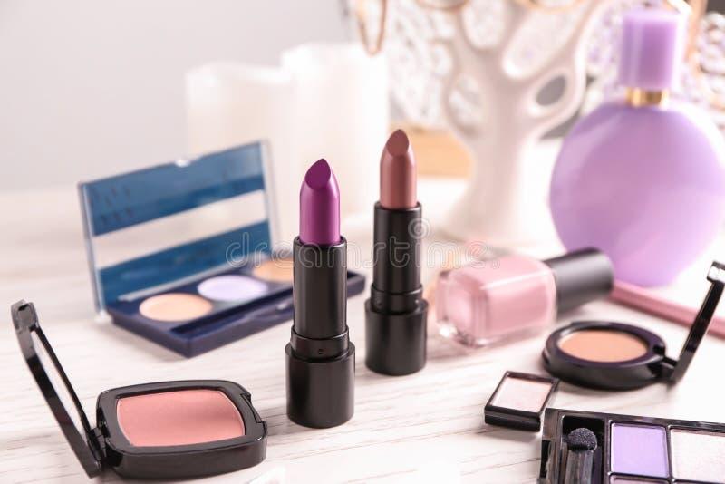 Barras de labios y otros cosméticos en la tabla fotografía de archivo