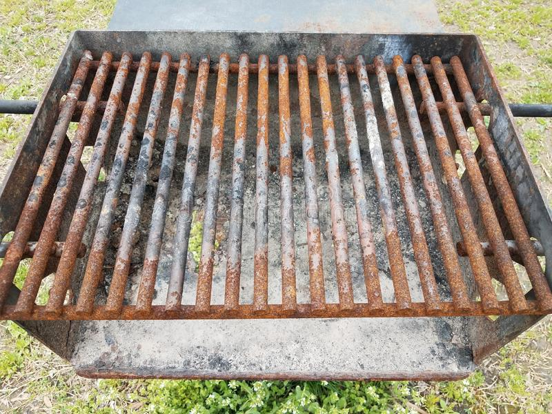 Barras de metal castanhas enferrujadas sobre grelhas de churrasco com fuligem e um buraco fotos de stock