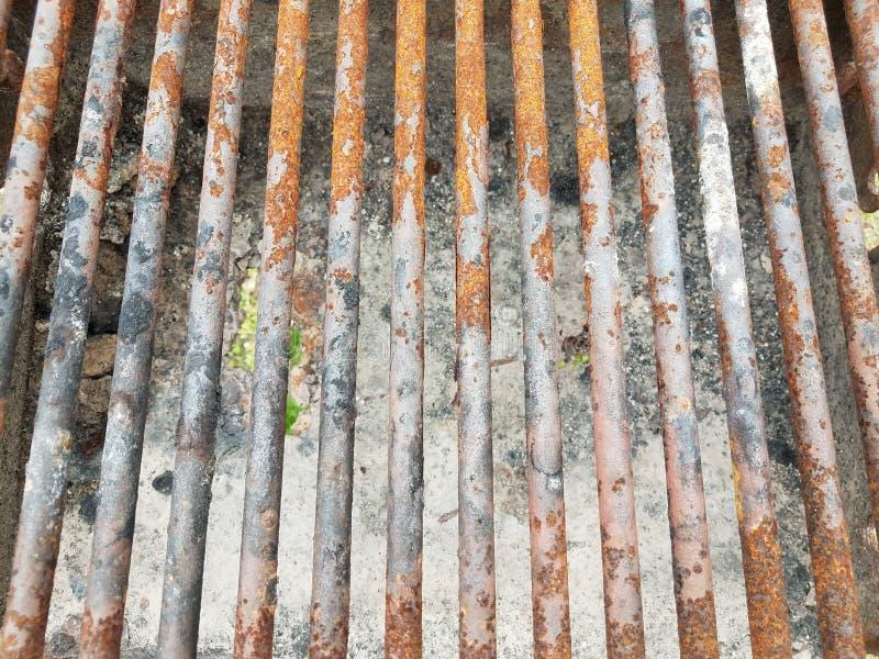 Barras de metal castanhas enferrujadas sobre grelhas de churrasco com fuligem e um buraco imagem de stock