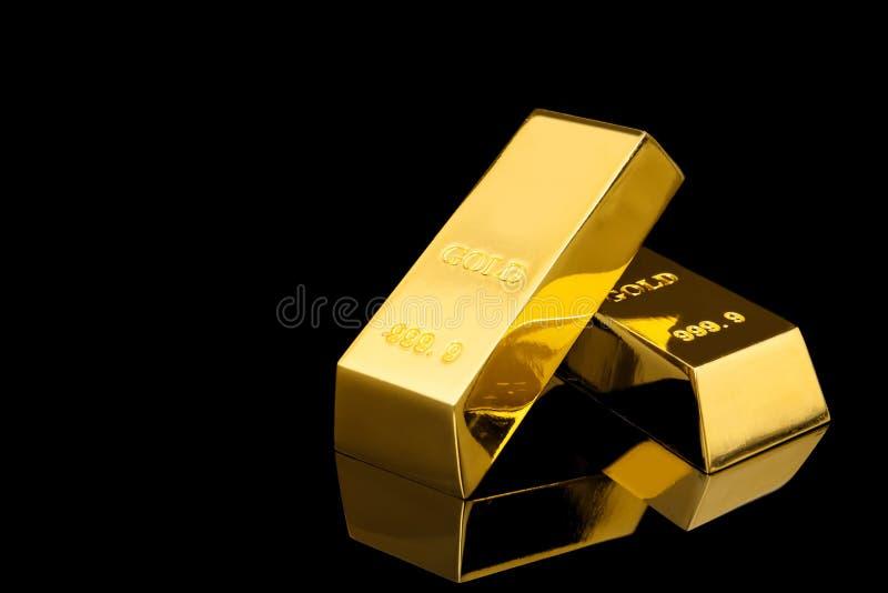 Barras de ouro brilhantes no fundo preto fotografia de stock royalty free