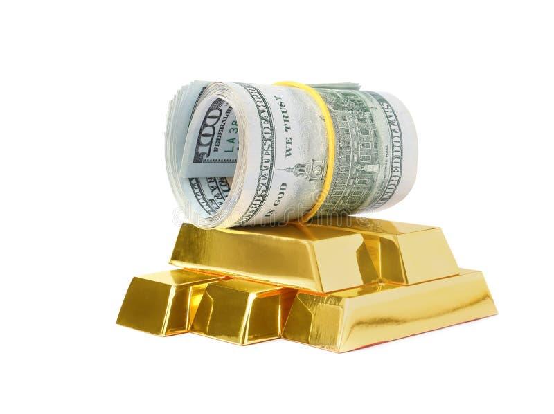 Barras de ouro e cédulas de brilho do dólar isoladas no branco foto de stock royalty free