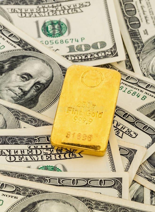Barras de ouro em notas de dólar foto de stock royalty free