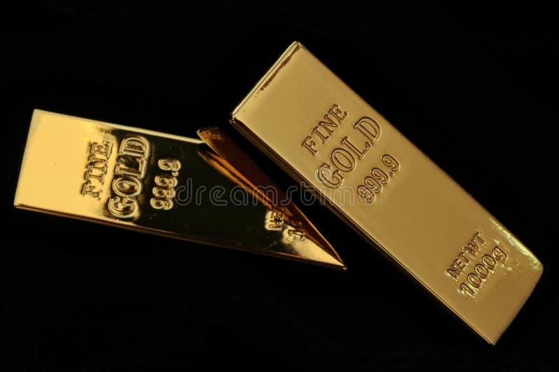Barras de ouro que pesam 1 quilograma, 2 varas empilhadas na escuridão, seletiva fotografia de stock royalty free