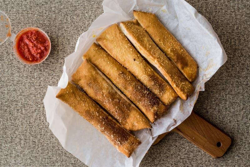 Barras de pan de ajo con la salsa y el queso parmesano de tomate foto de archivo
