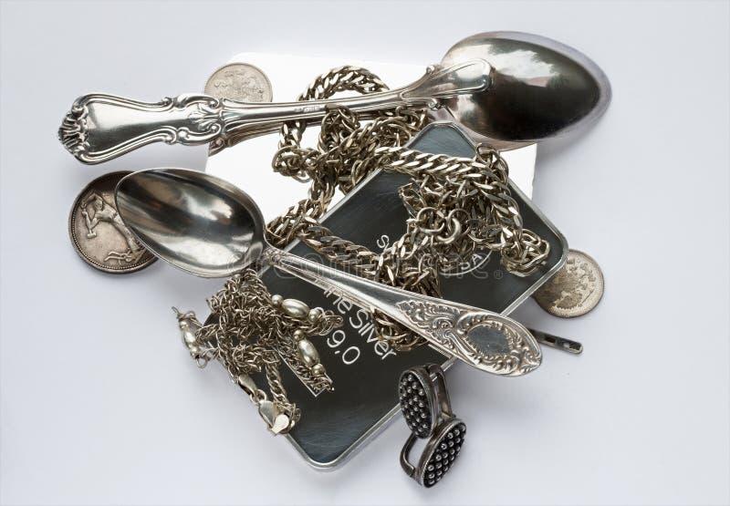 Barras de prata, moedas velhas, uma colher de chá, uma colher de café, brincos e correntes imagem de stock royalty free
