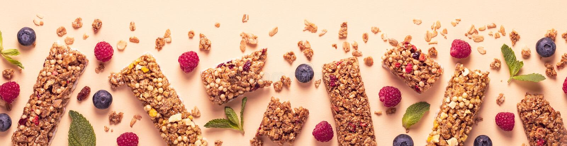 Barras del cereal en un fondo en colores pastel brillante fotos de archivo libres de regalías