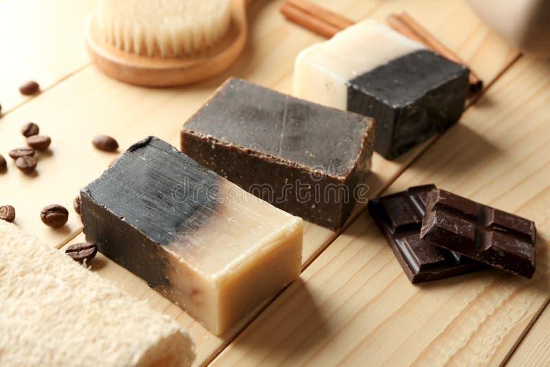 Barras del jabón con los pedazos del chocolate en la tabla de madera fotografía de archivo