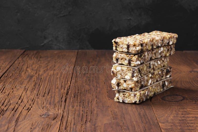 Barras do cereal com porcas, bagas e canela em um backgrou de madeira fotografia de stock royalty free