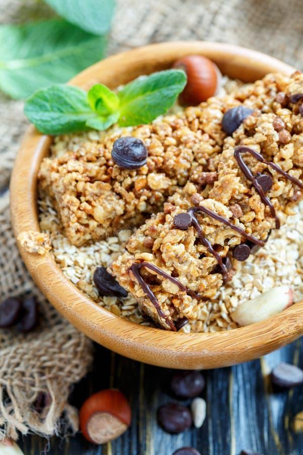 Barras do cereal com porcas e chocolate em uma bacia com flocos da aveia imagem de stock
