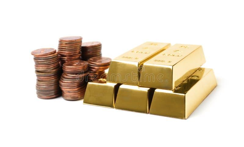 Barras e moedas de brilho de ouro no branco fotos de stock royalty free