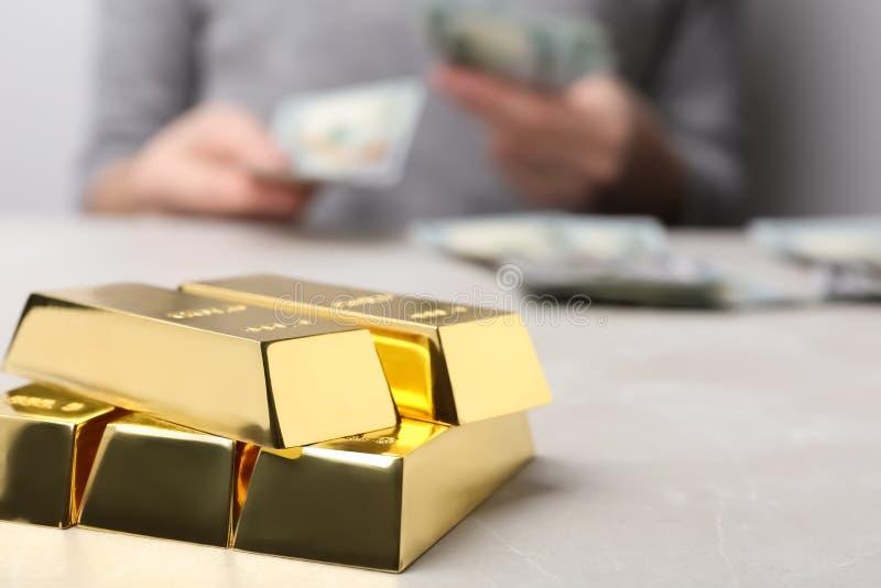 Barras e mulher de ouro empilhadas que contam o dinheiro na tabela, close up imagens de stock royalty free