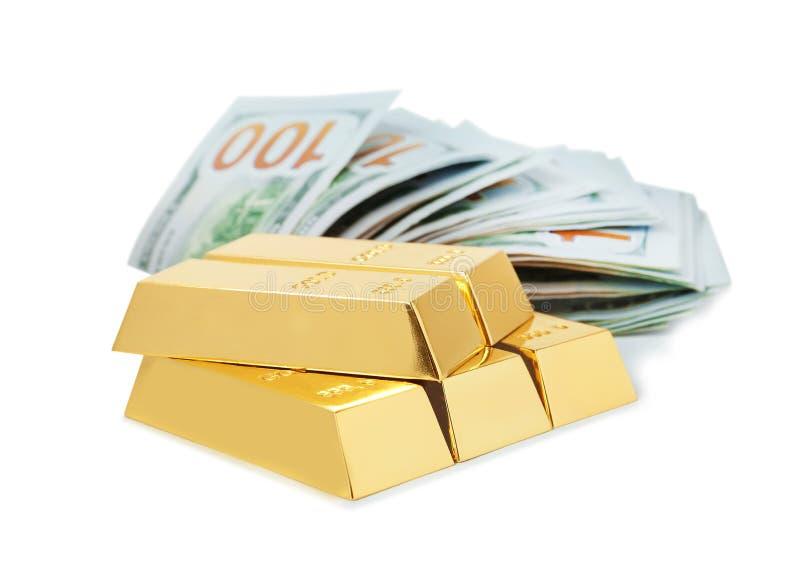 Barras e notas de dólar brilhantes de ouro no branco imagens de stock