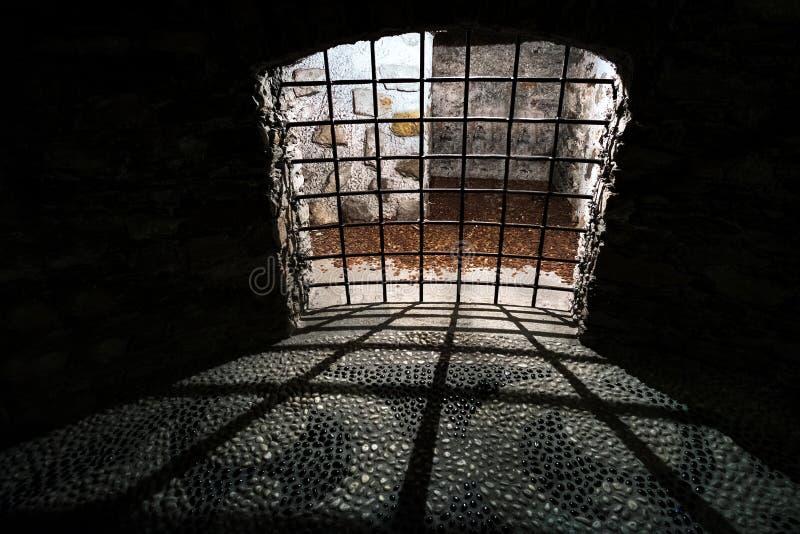 Barras medievales de la célula de la prisión oscura vieja de la mazmorra imagenes de archivo