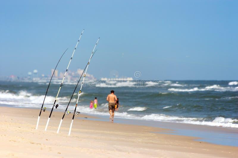 Barras que pescan con caña en la playa foto de archivo