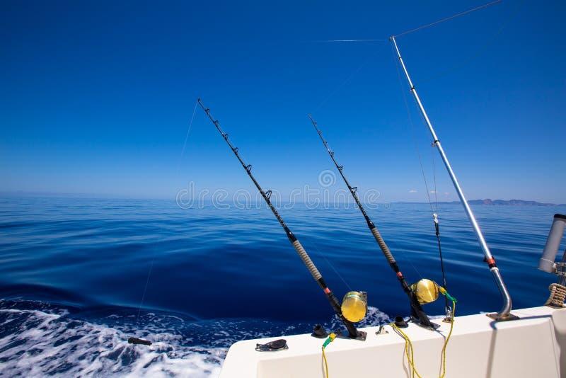 Barras y carretes de pesca con cebo de cuchara con cebo de cuchara del barco de pesca de Ibiza en el mar azul fotografía de archivo libre de regalías