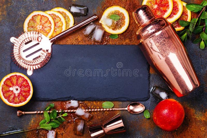Barre acessórios, ferramentas da bebida e ingredientes do cocktail na tabela de pedra oxidada estilo liso da configuração fotografia de stock