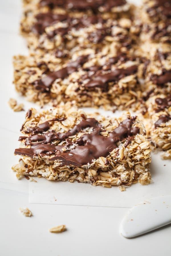 Barre casalinghe dell'avena del cioccolato su un fondo bianco Dessert sano del vegano, alimento della disintossicazione immagini stock