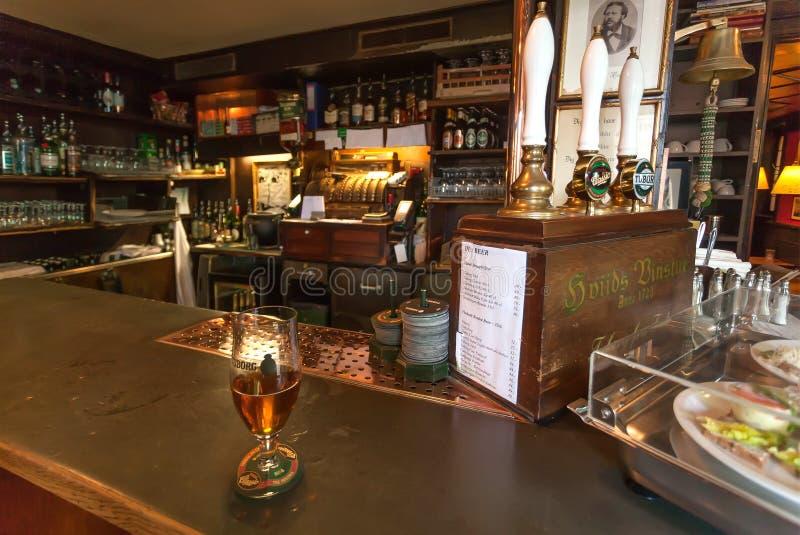 Barre contra com vidro da cerveja, do interior do vintage, de utensílios clássicos do estilo, de petiscos e de engarrafadores imagens de stock royalty free