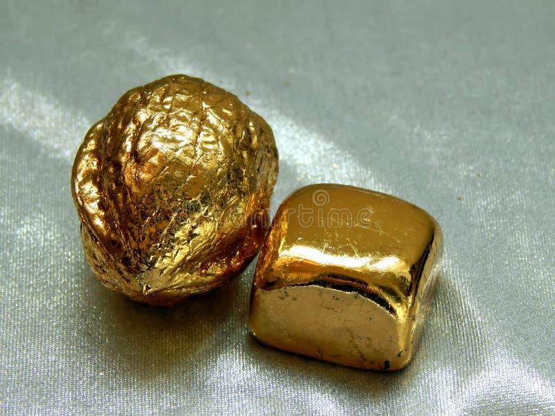 Barre d'or avec des écrous de noix sur un fond argenté photographie stock libre de droits