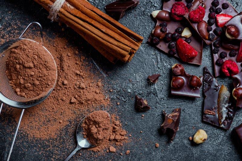 Barre de chocolat avec des écrous et des baies avec de la cannelle et le tamis photos stock