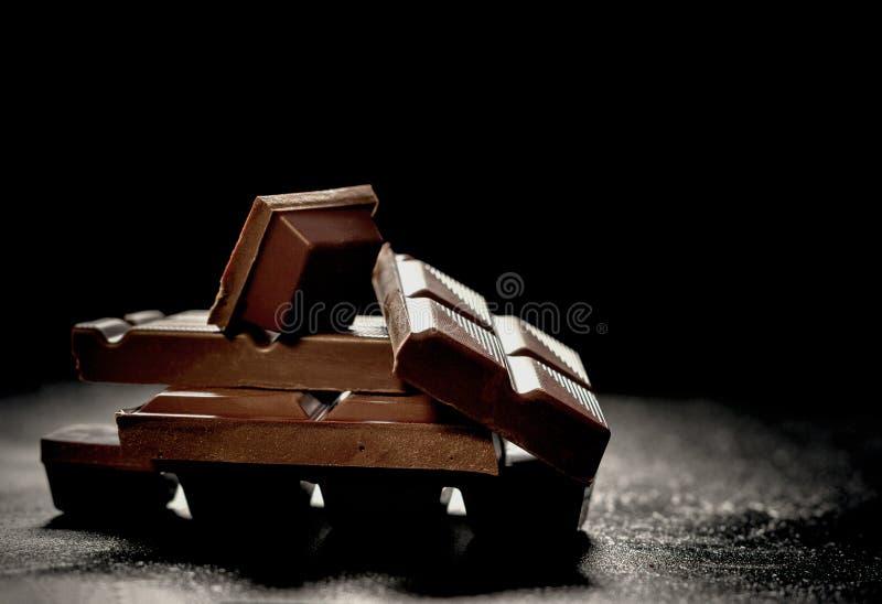 Barre de chocolat fonc?e criqu?e au fond noir photos stock