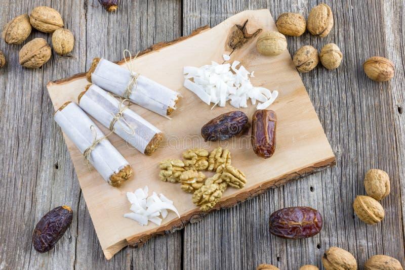 Barre de dates enveloppée en papier avec les noix et la noix de coco sur un en bois image stock