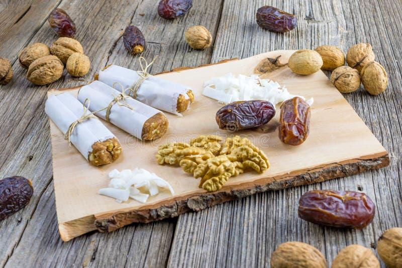 Barre de dates enveloppée en papier avec les noix et la noix de coco sur un en bois photographie stock libre de droits