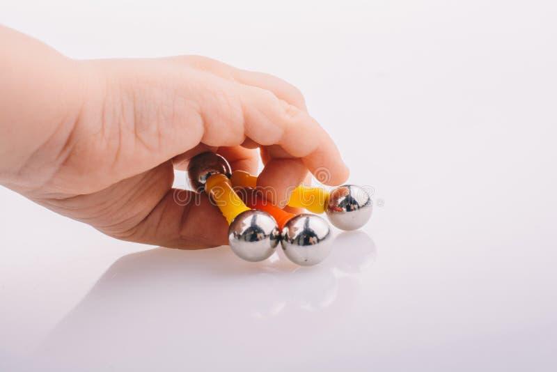 Barre del giocattolo del magnete della tenuta della mano e palle magnetiche sul backgro bianco fotografia stock