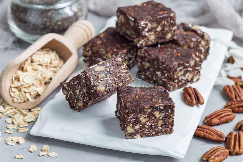 Barre di energia del cioccolato di Paleo con i fiocchi di avena, le noci americane, le date, i semi di chia ed i fiocchi della no fotografia stock